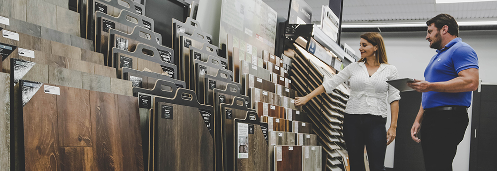 Flooring professional and client browsing flooring samples